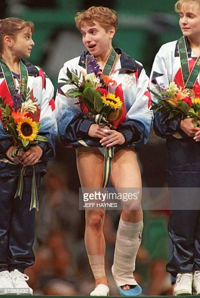 US gymnast Kerri Strug with a twisted ankle wears her gold medal as she is flanked by teammates Dominique Moceanu and Shannon Miller after the US won...