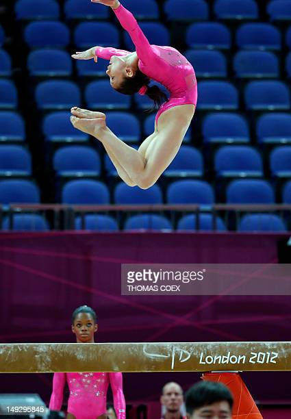 US gymnast Kyla Ross takes part in a training session as teammate Gabrielle Douglas looks on at 02 North Greenwich Arena in London on July 26 2012 on...