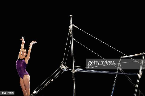 gymnast landing by uneven parallel bars - horizontal bars stock pictures, royalty-free photos & images