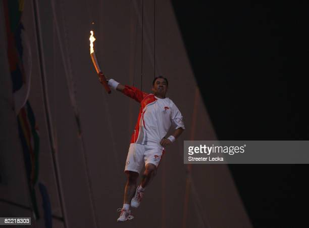 Gymnast Li Ning is lifted with the torch to light the Olympic Flame during the Opening Ceremony for the 2008 Beijing Summer Olympics at the National...