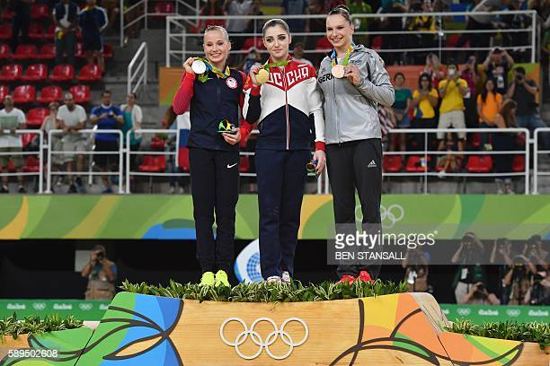 US gymnast Madison Kocian Russia's Aliya Mustafina and Germany's Sophie Scheder celebrate on the podium of the women's uneven bars event final of the...