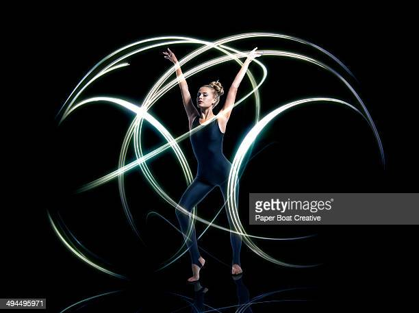 Gymnast making forms of large circular light rays