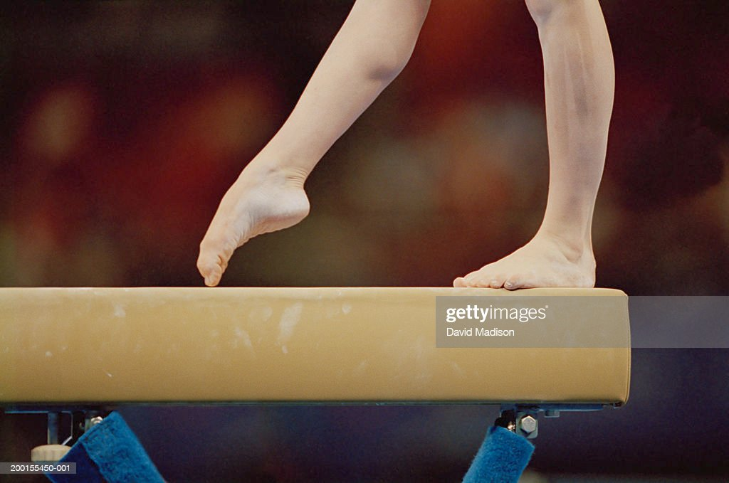 Gymnast on balance beam, low section, close-up : Stock Photo