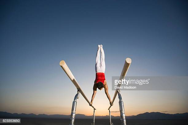 Gymnast Performing on Parallel Bars in the Desert