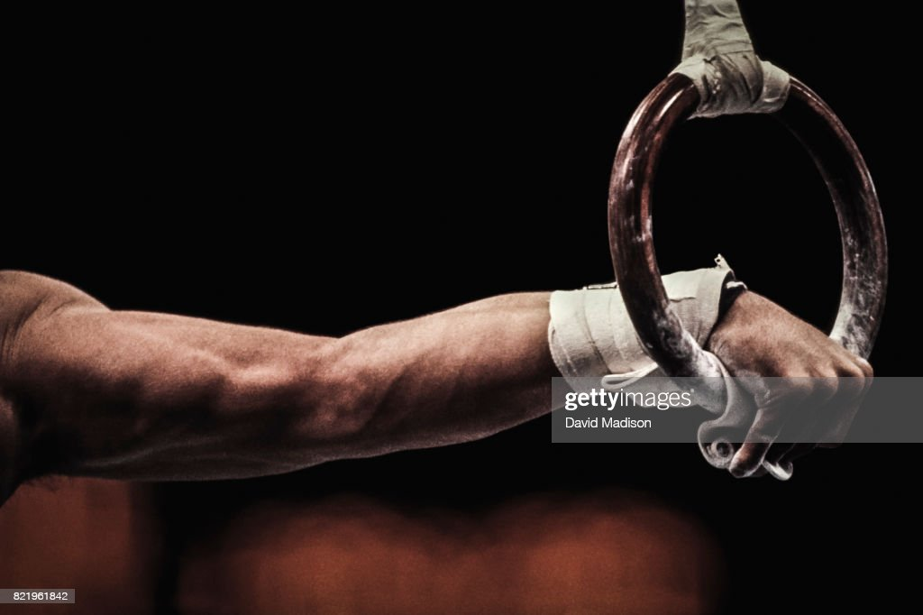 Gymnast performing on still rings : Stock Photo