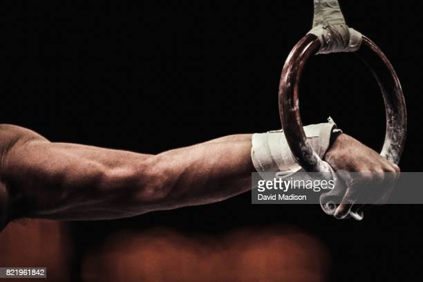 gymnast performing on still rings - gymnastique sportive photos et images de collection