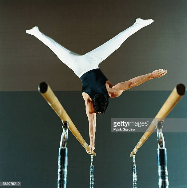 gymnast performing routine on parallel bars - parallel bars gymnastics equipment stock photos and pictures