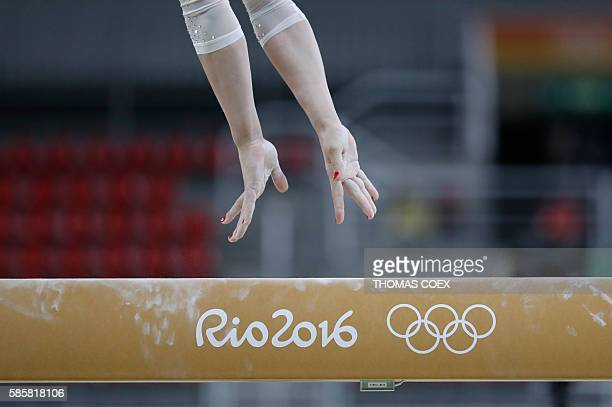 A gymnast practices on the balance beam of the women's Artistic gymnastics on August 4 2016 ahead of the Rio 2016 Olympic Games in Rio de Janeiro /...