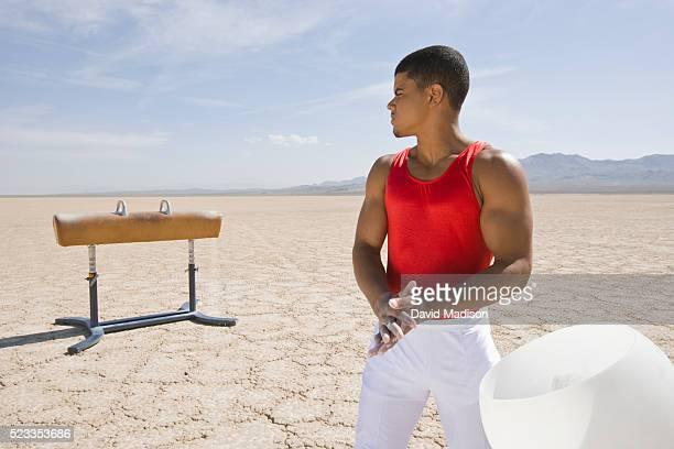 Gymnast Putting Chalk on Hands Beside a Pommel Horse in the Desert