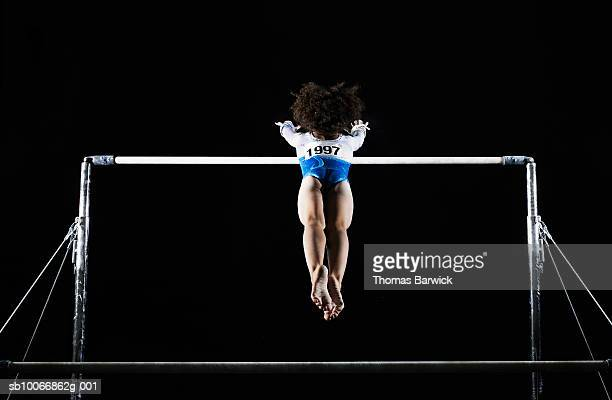 gymnast (9-10) reaching for uneven bars - horizontal bars stock pictures, royalty-free photos & images