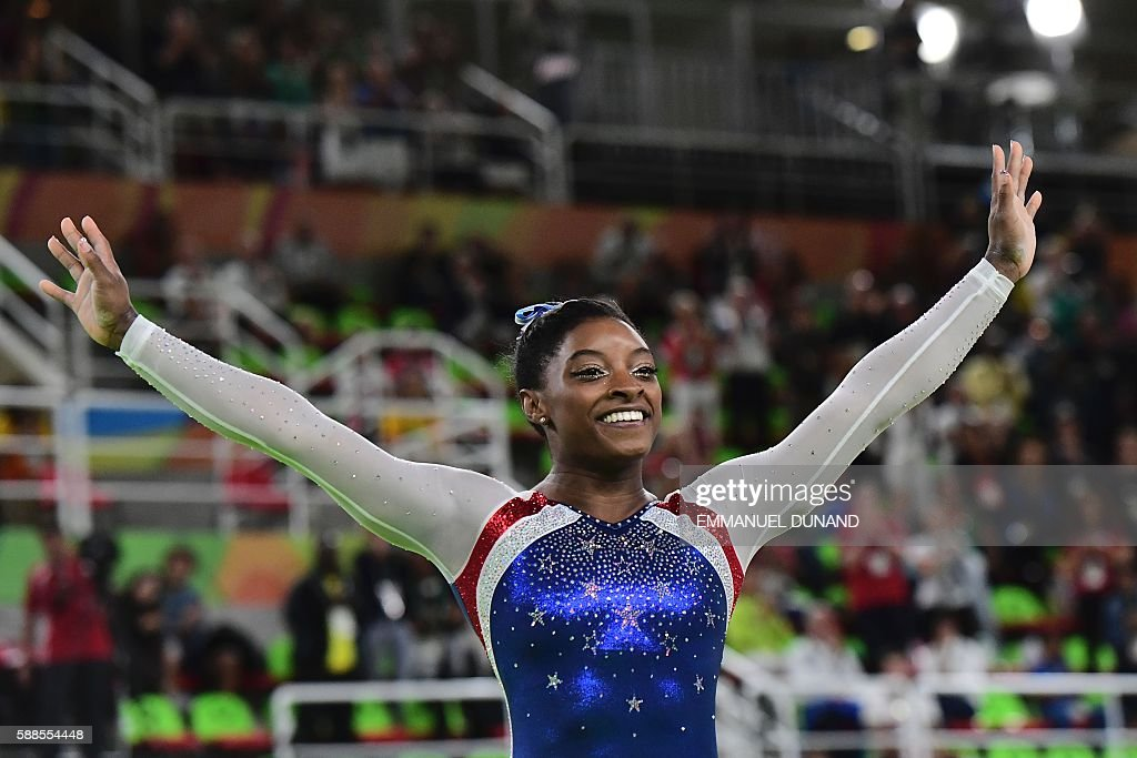US gymnast Simone Biles celebrates after the women's individual all-around final of the Artistic Gymnastics at the Olympic Arena during the Rio 2016 Olympic Games in Rio de Janeiro on August 11, 2016. US gymnast Simone Biles won the event ahead of her compatiot Alexandra Raisman and Russia's Aliya Mustafina. / AFP / Emmanuel DUNAND