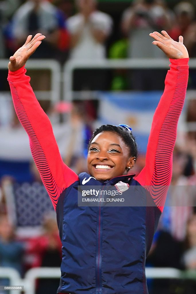 US gymnast Simone Biles celebrates on the podium after the women's individual all-around final of the Artistic Gymnastics at the Olympic Arena during the Rio 2016 Olympic Games in Rio de Janeiro on August 11, 2016. US gymnast Simone Biles won the event ahead of her compatiot Alexandra Raisman and Russia's Aliya Mustafina. / AFP / EMMANUEL