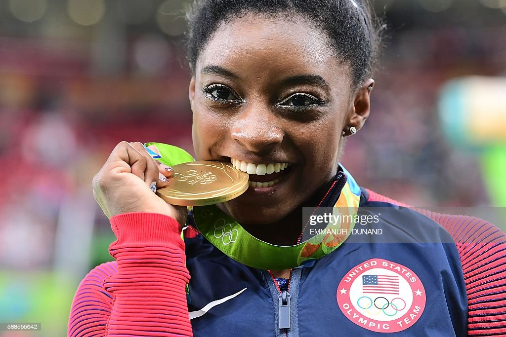 TOPSHOT - US gymnast Simone Biles celebrates with her gold medal after the women's individual all-around final of the Artistic Gymnastics at the Olympic Arena during the Rio 2016 Olympic Games in Rio de Janeiro on August 11, 2016. US gymnast Simone Biles won the event ahead of her compatiot Alexandra Raisman and Russia's Aliya Mustafina. / AFP / Emmanuel DUNAND
