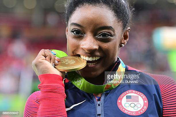 TOPSHOT US gymnast Simone Biles celebrates with her gold medal after the women's individual allaround final of the Artistic Gymnastics at the Olympic...