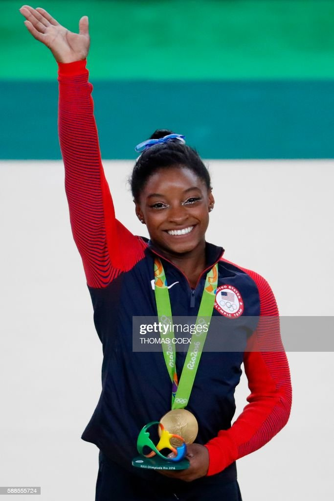 TOPSHOT - US gymnast Simone Biles celebrates with her gold medal on the podium after the women's individual all-around final of the Artistic Gymnastics at the Olympic Arena during the Rio 2016 Olympic Games in Rio de Janeiro on August 11, 2016. US gymnast Simone Biles won the event ahead of her compatiot Alexandra Raisman and Russia's Aliya Mustafina. / AFP PHOTO / Thomas COEX
