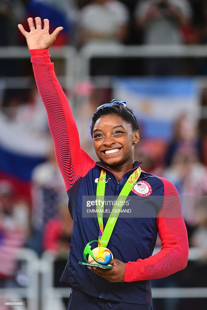 US gymnast Simone Biles celebrates with her gold medal on the podium after the women's individual all-around final of the Artistic Gymnastics at the Olympic Arena during the Rio 2016 Olympic Games in Rio de Janeiro on August 11, 2016. US gymnast Simone Biles won the event ahead of her compatiot Alexandra Raisman and Russia's Aliya Mustafina. / AFP / EMMANUEL