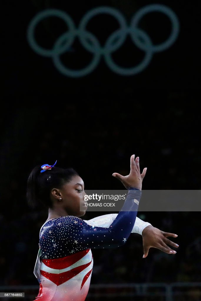 TOPSHOT - US gymnast Simone Biles competes in the Beam event during the women's team final Artistic Gymnastics at the Olympic Arena during the Rio 2016 Olympic Games in Rio de Janeiro on August 9, 2016. / AFP PHOTO / Thomas COEX