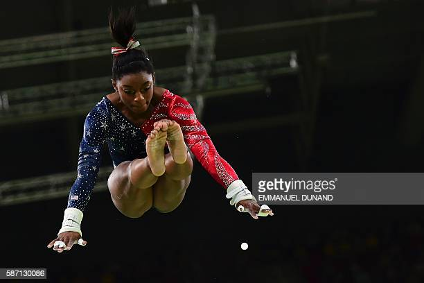 US gymnast Simone Biles competes in the qualifying for the women's Uneven Bars event of the Artistic Gymnastics at the Olympic Arena during the Rio...