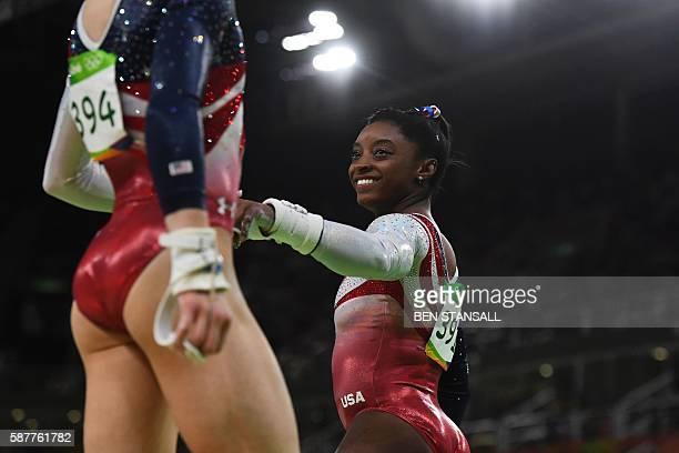 TOPSHOT US gymnast Simone Biles fist bums her teammate Madison Kocian before she competes in the Uneven Bars event during the women's team final...