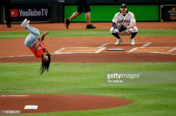 Gymnast Simone Biles performs a flip after throwing out the ceremonial first pitch prior to Game Two of the 2019 World Series between the Houston...