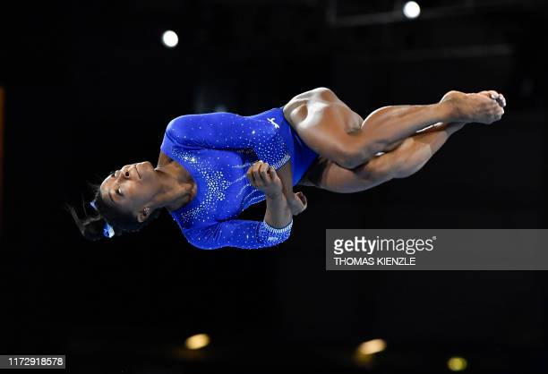 Gymnast Simone Biles turns in the air as she performs on the floor during a training session at the FIG Artistic Gymnastics World Championships in...
