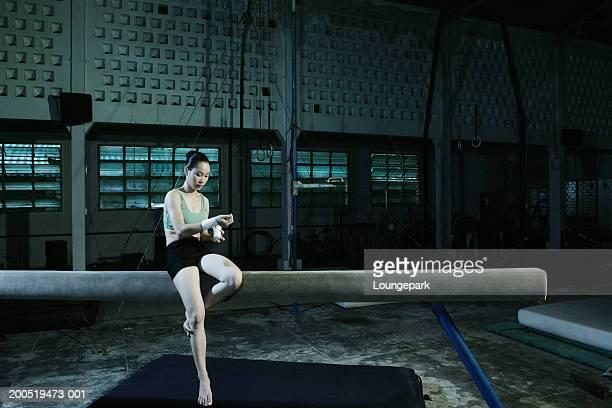 Gymnast sitting on beam bandaging wrist