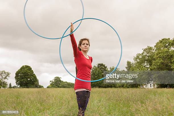 Gymnast spins hulahoops around hand in midair.