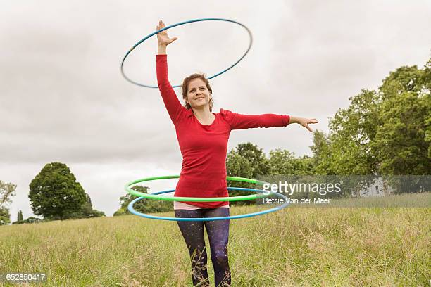 Gymnast spins hulahoops on  waist and hand.