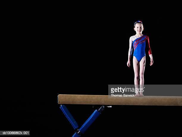 Gymnast (9-10) standing on balance beam