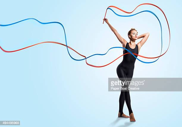 Gymnast waving blue and red ribbons