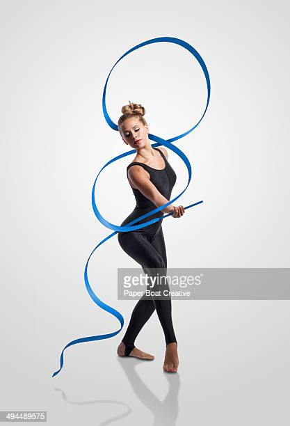 Gymnast waving blue ribbon around her body