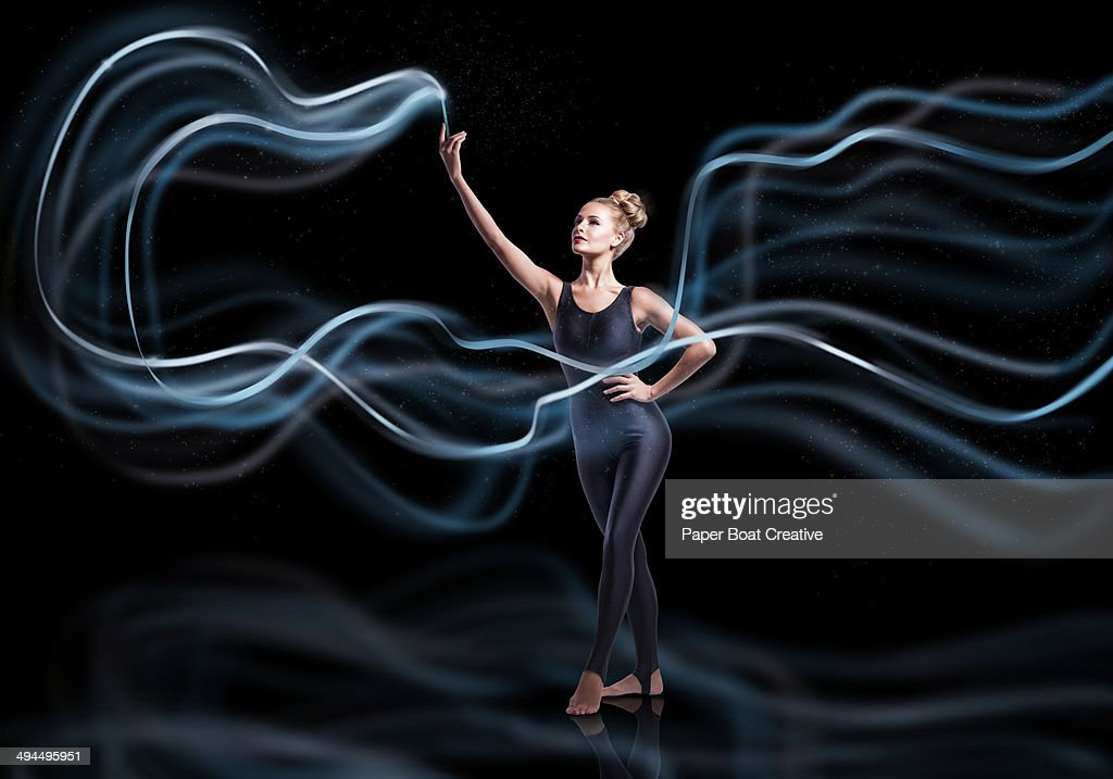 Gymnast waving blue ribbons with high speed motion : Stock Photo