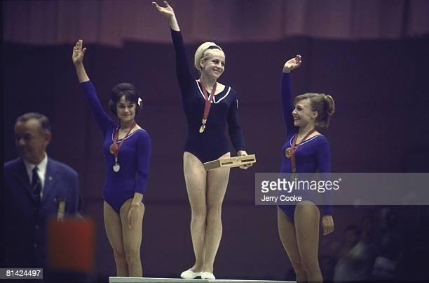 Gymnastics 1968 Summer Olympics USR Zinaida Voronina CZE Vera Caslavska and USR Natalya Kuchinskaya victorious with medal on stand during all around...
