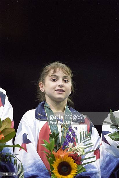 1996 Summer Olympics USA Dominique Moceanu victorious with gold medal on stand during ceremony after winning Team All Around Final at Georgia Dome...