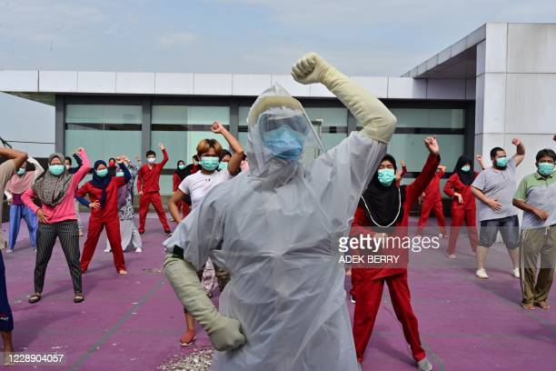 Gymnastics instructor wearing personal protective equipment leads a morning exercise for patients of the COVID-19 coronavirus at a hotel designated...