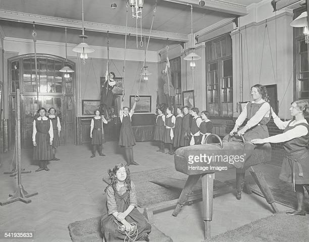 Gymnastics lesson Laxon Street Evening Institute for Women London 1914 Girls using the horse and ropes with one girl in the foreground with a...