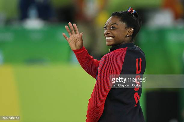 Day 11 Simone Biles of the United States waves to someone in the audience while waiting on the podium to receive her gold medal after winning the...