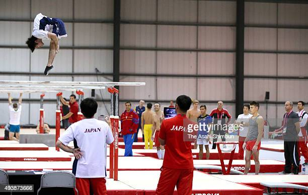 Gymnasts and staffs watch Kohei Uchimura of Japan performing in Parallel Bars during a practice session ahead of the World Artistic Gymnastics...