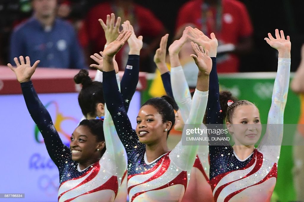 TOPSHOT - US gymnasts celebrate after the women's team final Artistic Gymnastics at the Olympic Arena during the Rio 2016 Olympic Games in Rio de Janeiro on August 9, 2016. / AFP / Emmanuel DUNAND