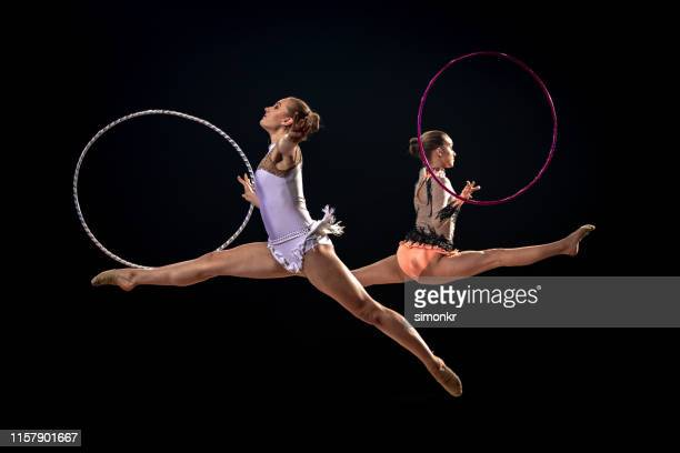 gymnasts doing rhythmic gymnastics with hoop - rhythmic gymnastics stock pictures, royalty-free photos & images