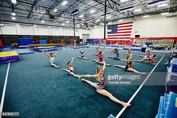 gymnasts doing splits in gym while warming up - legs apart stock pictures, royalty-free photos & images