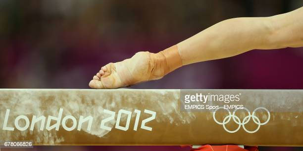 A gymnasts foot balances on the high beam