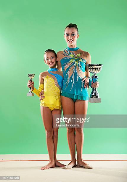 2 gymnasts holding trophies, looking at camera - leotard stock pictures, royalty-free photos & images