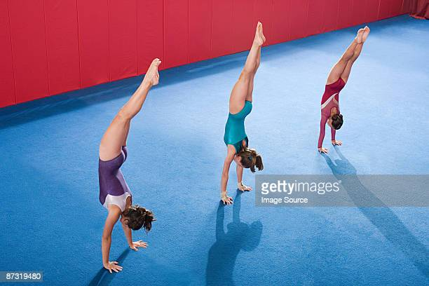 Gymnasts in a row doing handstands