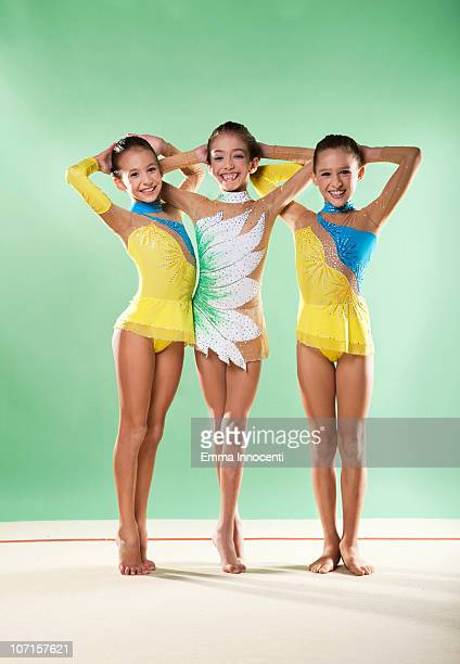 3 gymnasts standing, smiling, arms behind  head - legs crossed at ankle stock pictures, royalty-free photos & images
