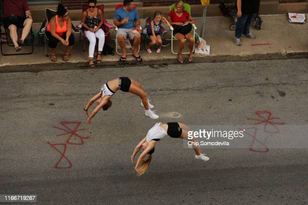 Gymnasts turn flips as they march in the Iowa State Fair Parade along Grand Avenue in downtown August 07 2019 in Des Moines Iowa Politicians seeking...