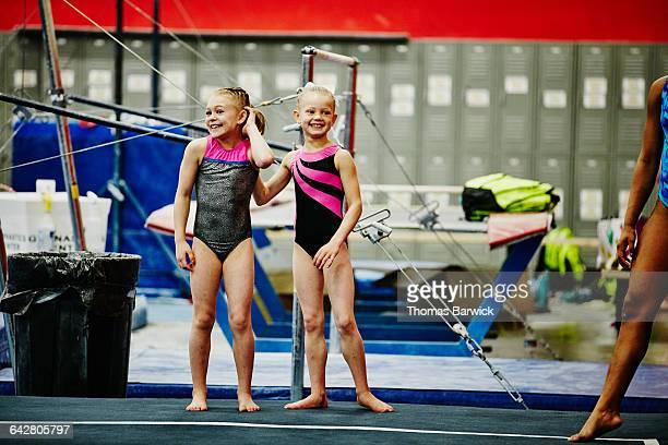 gymnasts watching teammates perform floor routine - artist stock-fotos und bilder