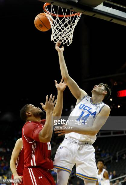 Gyorgy Goloman of the UCLA Bruins grabs a rebound over Charles Thomas IV of the Wisconsin Badgers during the National Collegiate Basketball Hall Of...