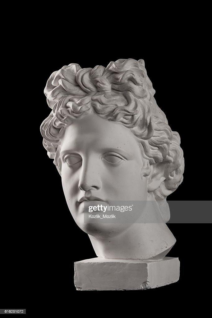 Gypsum statue of Apollo's head on a black background : Stock Photo