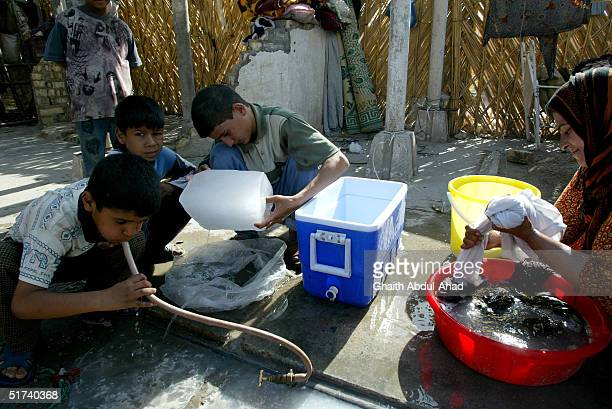 Gypsy boys drink from a tap as their mother washes clothes in their family home in a former Air Force base on November 14 2004 in Baghdad Iraq The...